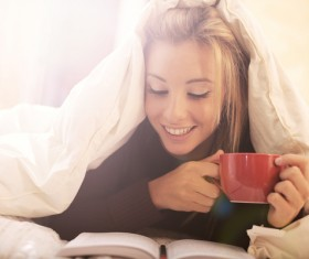 Lying in bed drinking coffee reading girl Stock Photo 01