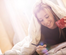Lying in bed drinking coffee reading girl Stock Photo 02