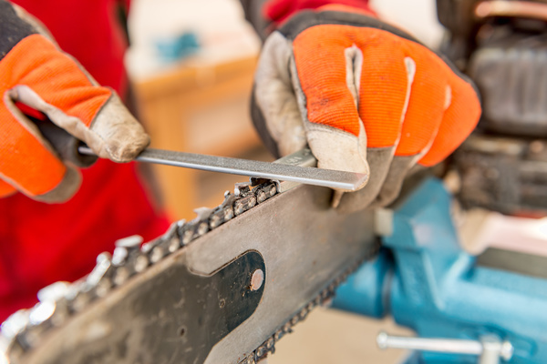 Sharpening a chainsaw Close up on a man sharpening a chainsaw chain with file.