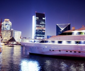 Moored yacht with a brightly lit city Stock Photo