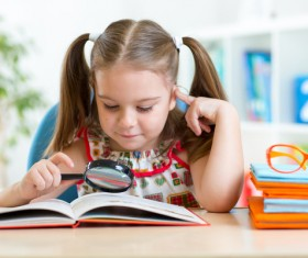 Pre-school children who read books with magnifying glass Stock Photo