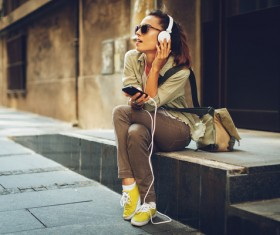 Sitting on the street listening to music Stock Photo
