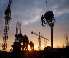 Sunset busy construction workers Stock Photo