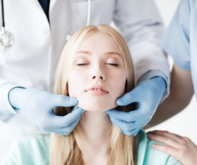 The doctor checks the patients tonsils Stock Photo