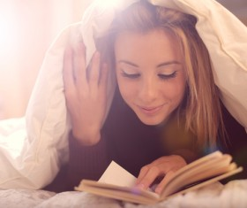 The girl lying on the bed reading Stock Photo 02