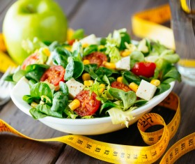 Vegetable salad and tape measure on the table Stock Photo