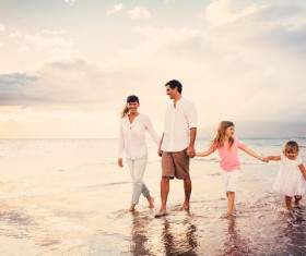 Walking on the beach a happy family of four Stock Photo