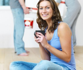 Woman sitting on the floor drinking coffee Stock Photo