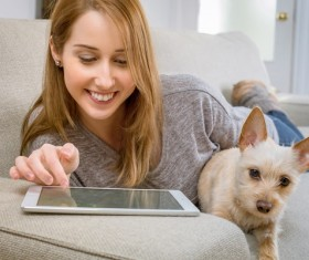 A girl and a pet dog lying on a sofa playing with a tablet computer Stock Photo