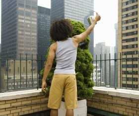 A young man who watered the plants on the balcony Stock Photo