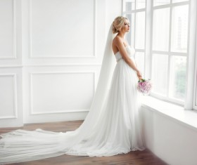 Beautiful bride standing at the window Stock Photo