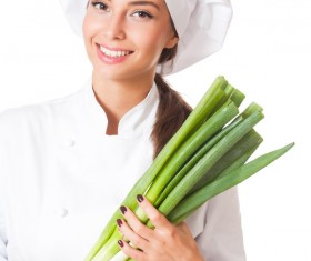 Beautiful female chef holding a green onions Stock Photo