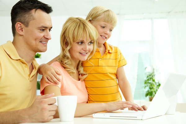 Happy family using a computer together Stock Photo
