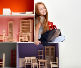 Happy little girl playing doll house filled with mini furniture toys Stock Photo 01