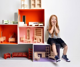 Happy little girl playing doll house filled with mini furniture toys Stock Photo 02