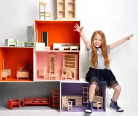 Happy little girl playing doll house filled with mini furniture toys Stock Photo 03