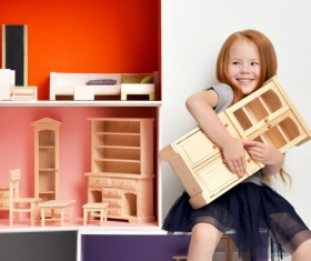 Happy little girl playing doll house filled with mini furniture toys Stock Photo 04