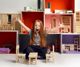 Happy little girl playing doll house filled with mini furniture toys Stock Photo 06
