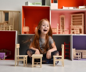 Happy little girl playing doll house filled with mini furniture toys Stock Photo 07