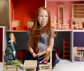 Happy little girl playing doll house filled with mini furniture toys Stock Photo 10