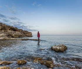 Lonely woman posing on rocky calm beach Stock Photo