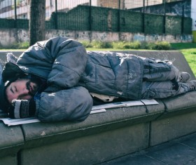 Lying on the bench to sleep on the beggar Stock Photo
