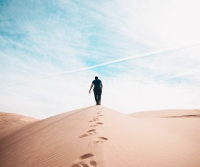 Man walking alone on dune Stock Photo