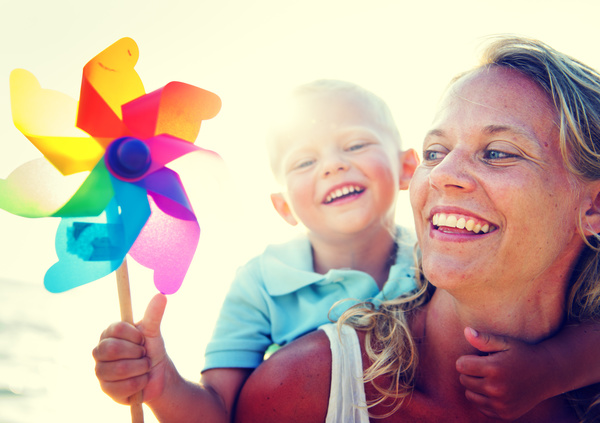 Mother carrying a small windmill with a child Stock Photo