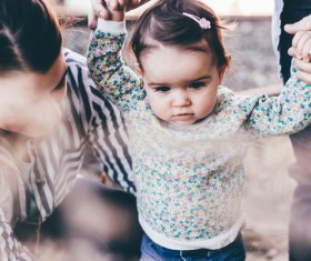 Parents take care of the little girl walking Stock Photo