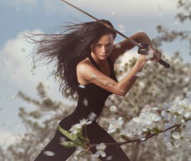 Sword wielding girls and white cherry blossoms Stock Photo