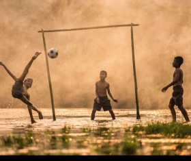 The children who play football in the water Stock Photo