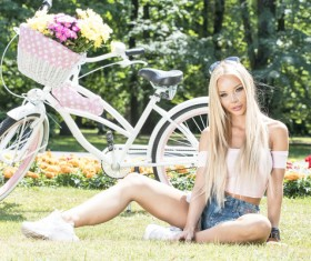 The girl sitting on the grass and the bike behind her Stock Photo