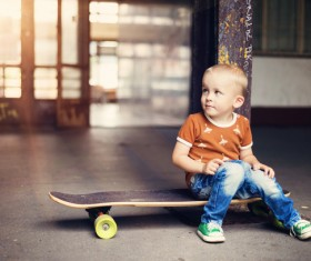 The little boy sitting on the skateboard Stock Photo