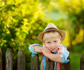 The little boy standing next to the fence Stock Photo