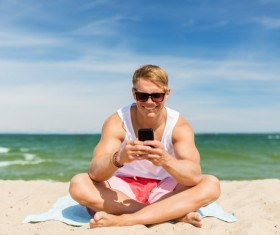 The man sitting on the beach plays the smartphone Stock Photo