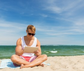 The man sitting on the beach plays the tablet Stock Photo