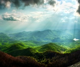 The sunlight penetrated the black clouds round the mountains Stock Photo
