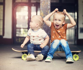 The two little boys sitting on the skateboard Stock Photo