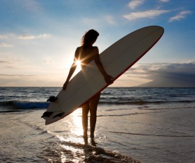 The woman holding the surfboard stands on the beach Stock Photo