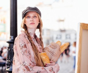 The young girl holding the bread on the street Stock Photo 03