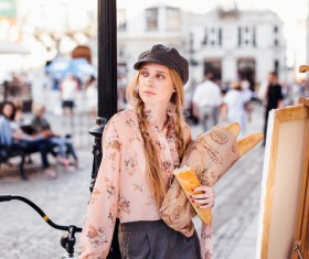 The young girl holding the bread on the street Stock Photo 05