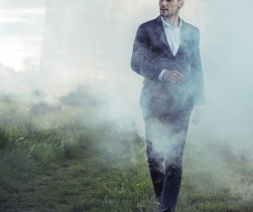 Walking handsome man in thick fog Stock Photo 01