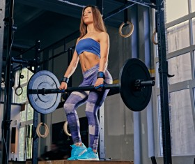 Woman in the gym lifting barbell Stock Photo 13