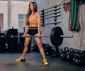 Woman in the gym lifting barbell Stock Photo 16