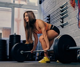 Woman in the gym lifting barbell Stock Photo 17
