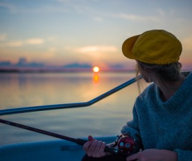 Young woman fishing on lake at sunset Stock Photo
