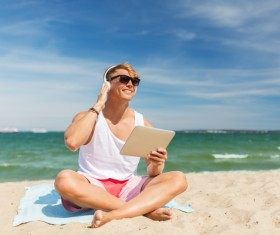 man sitting on the beach listening to music with a Tablet PC Stock Photo