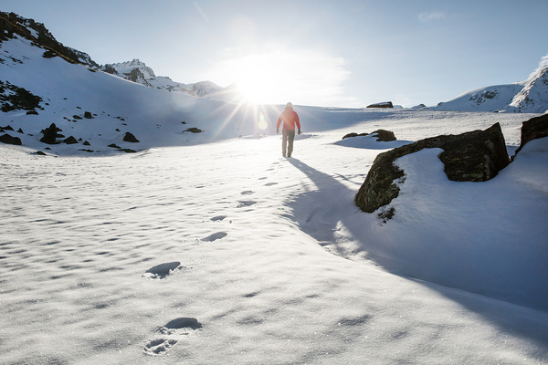 Human walking on snowy mountain land under sunlight Stock Photo