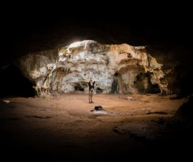 Lonely woman in stone cave Stock Photo