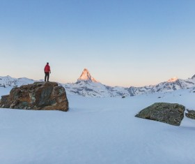 Man standing on rocky snow mountain Stock Photo